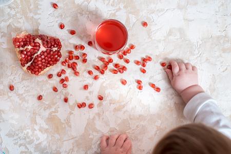 Handful of pomegranate seeds on a babys hand. Фото со стока