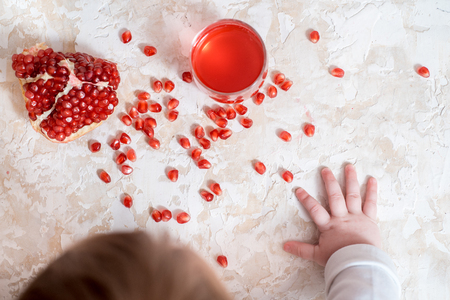 Handful of pomegranate seeds on a babys hand. flat lay concept. Baby hands Imagens