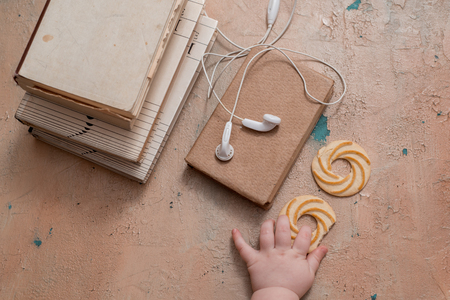 Audio book concept. Headphones, coffee and book over wooden table. Top view with space for your text. little baby pens take a book round biscuits and tea
