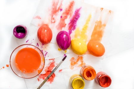 the process of coloring eggs for Easter. multicolored paint on paper. Bright eggs are yellow, orange, red and purple. Stock Photo