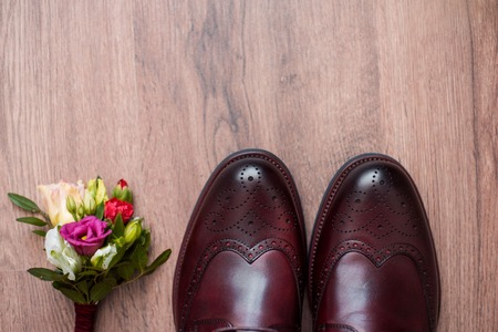 Close up of modern man accessories. leather shoes, belt and flower boutonniere on rustic background. Set for formal style of wearing isolated on white background.