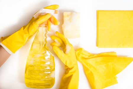 Cleaning concept - mixed detergents and cleaning yellow accessories on a white background. Women's hands in rubber yellow gloves. Top view. Copy space. Flat lay