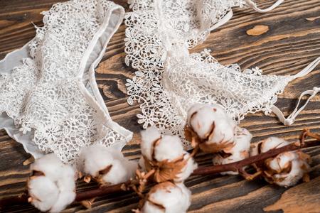 Mutandine di cotone a righe e reggiseno bianco. La biancheria femminile sullo sfondo concreto. Colpo di vista dall'alto di biancheria intima da donna alla moda. Tessuto morbido naturale