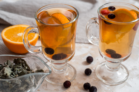 fruit orange tea with mint and melissa. Berries of black currant and raspberry, orange slices in a glass cup. Stock Photo
