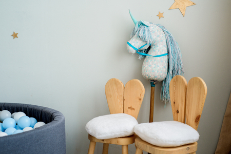 Child dream concept. Cosy bedroom decorated with toys and stars. Unicorn pillow, toy horse and two children's chairs in the form of a hare. copy space