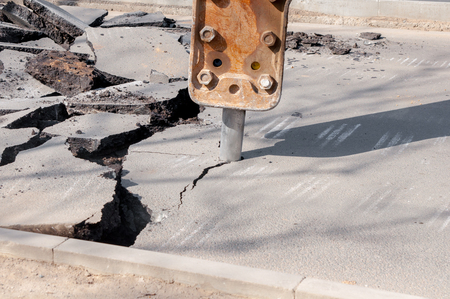 Road repairing works with jackhammer. machine drills asphalt. Large fragments of land and pits everywhere on the road. working equipment with a drill works loudly 版權商用圖片
