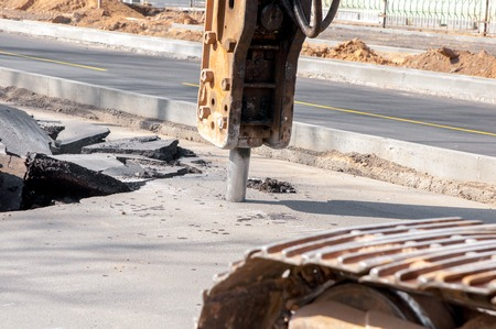 The machine drills asphalt. Male worker repairing driveway surface with jackhammer, digging and drilling concrete roads Reklamní fotografie