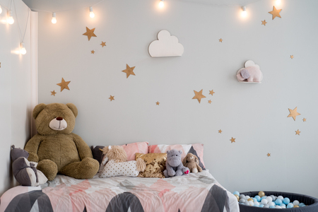 Teddy bear between paper bags and wooden chairs in child's room