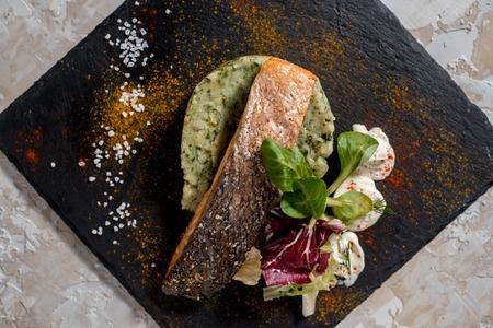 Roasted salmon fish steak with potato, sauce in white plate on dark background Stock Photo