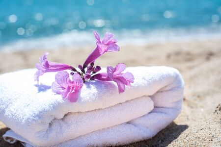 White towels and flowers with ocean scene. Stacked white spa towels on the blue Indian ocean background. Maldives luxury resort vacation. Fluffy white towels on table near sea. Luxury hotel vacation.