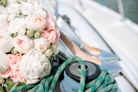 Wedding shoes of the bride alongside with the garden bouquet on the yacht in the sea.