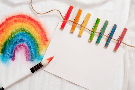 Painting of rainbow on notebook or sketch book with paintbrush on wooden planks
