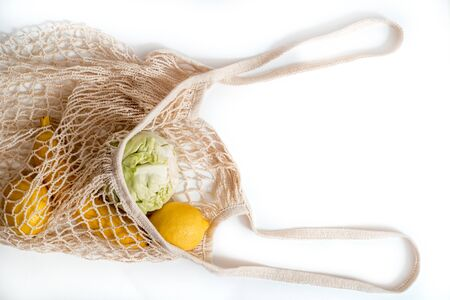 fresh fruits and vegetables reusable packaging. Lemon and banana, fresh cabbage on a white background. Bag - string bag. Zero Vaste concept, vitamin and vitamin deficiency concept 免版税图像