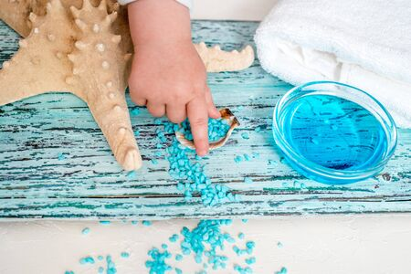 blue salt for spa. white towel, blue soap, starfish and seashells. Sea Spa Concept. rest and relaxation, thalassotherapy. Children's hands take the shell and salt