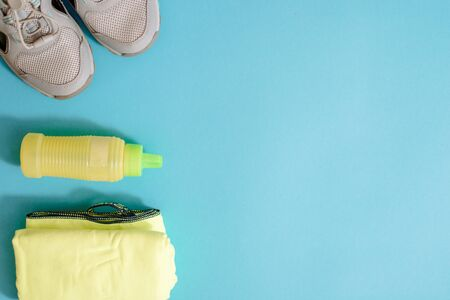 Flat lay shot of Sport equipment. Sports, running shoes, headphones, a glass of clean water and a microfiber towel on blue background. copy space