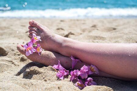 Nackte Füße am Strand, gelber Sand, eine exotische Blume an den Fußspitzen, heiße Sonne, blaues Meer. Sommer und Ferien Standard-Bild