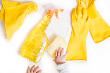 Cleaning concept .cleaning yellow accessories on a white background. rubber yellow gloves. Baby hands.Top view. Copy space. Flat lay