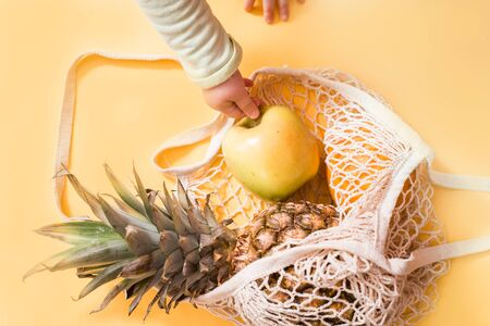 Mesh shopping bag with lemons and pineapple . Zero Wast. Pineapple, apple and orange on a yellow-pink background. Summer concept. Baby hand takes an apple