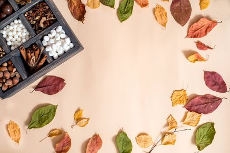 Wooden box with sweets,chocolate and cookies. Nuts, spices and orange for making mulled wine.bright leaves. The concept of a cozy sweet autumn. Flat lay, top view, copy space