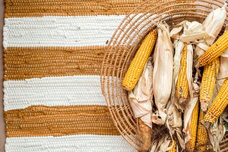 Dry corn, ear of corn. Yellow leaves in a wicker basket. Striped background, cotton knitted rug red carpet. cozy warm autumn. flat lay. top view. Vegetarian, healthy, clean eating,diet concept Stock fotó