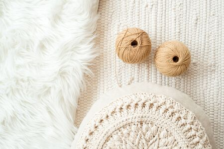 threads, crocheted round napkin.Balls of thread in a wicker box. White napkin like a flower. on a fur white background and knitted light background. cozy home and handmade concept.