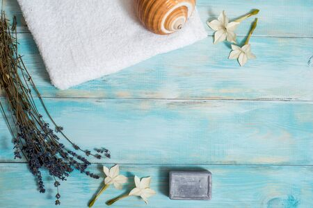 Sea spa, white towel, blue wooden old background. lavender and dry lotus flowers. sea shell. Purple bath soap. Vacation concept. copy space.