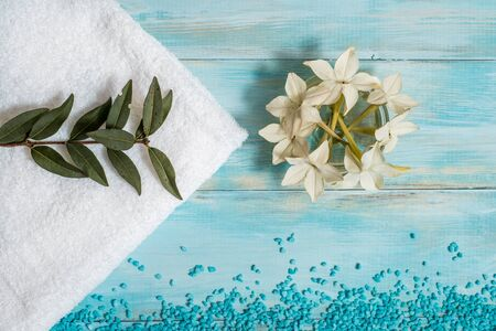 Spa and wellness setting with flowers, and white towel on old wooden Imagens