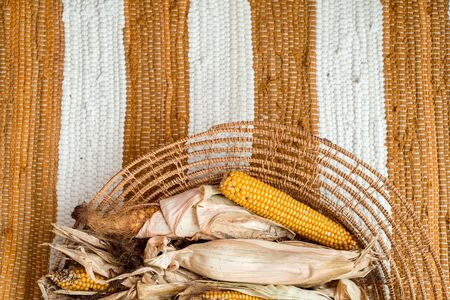 Dry corn, ear of corn. Yellow leaves in a wicker basket. Striped background, cotton knitted rug red carpet. cozy warm autumn. flat lay. top view. Vegetarian, healthy, clean eating,diet concept Stockfoto