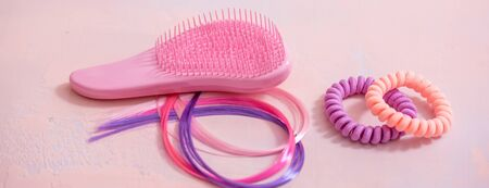 long banner light pink comb, purple decorative hair for girls hairstyles. Decoration for teenage girls. Silicone rubber band.copy space. flat lay. top view Stockfoto