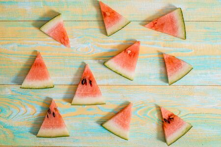 Slices of watermelon on old blue and yellow wooden background. Chopped watermelon. summer, harvest and vacation concept. Flat lay, top view Banco de Imagens