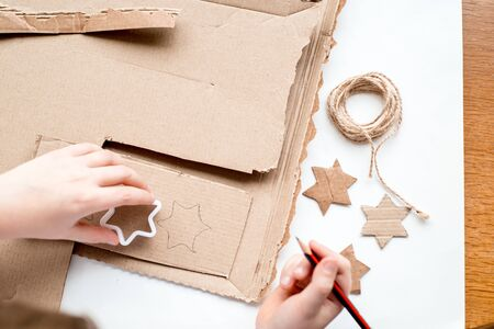 A child carves a star from cardboard. Christmas decoration, Christmas garland, hand made and Zero waste. Hands of a child on a white background. Div. Flat lay, top view, copy space