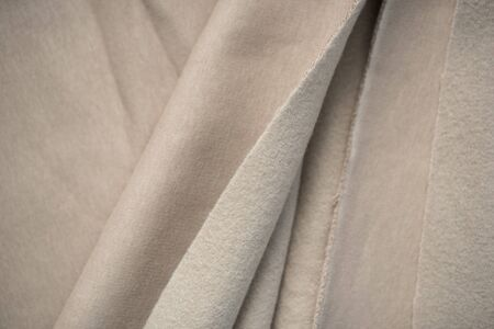 Woolen beige knitted fabric in soft folds. Texture as a background. Sewing pattern. Cut cotton piece. Stockfoto