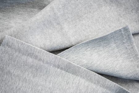 Woolen gray knitted fabric in soft folds. Texture as a background. Sewing pattern. Cut cotton piece