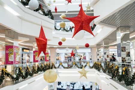 2019, December 3, Minsk, Belarus, Dana Mall.Shopping center decorated with christmas ornaments and lights. Red stars, lots of people shopping