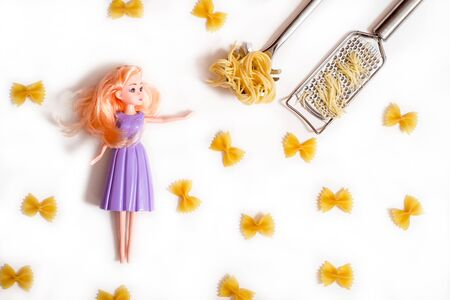 lady doll.purple clothes is cooking pasta. Raw pasta and cheese. Metal cheese grater. slotted spoon. Cute teen girl pasta bows.Ingredients for carbonara,isolated on white Copy space top view flat lay