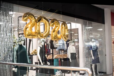 2020 gold numbers, shopping in the metropolis. shop windows. manikins with clothes and sales. New Year sale, buying gifts for holidays.