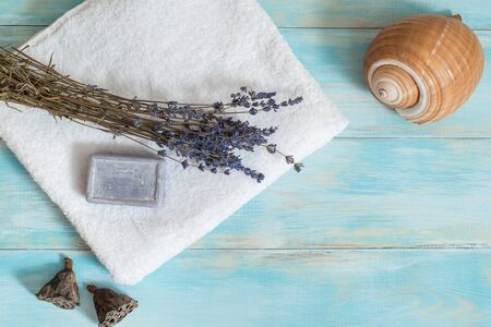 Sea spa, white towel, blue wooden old background. lavender and dry lotus flowers. sea shell. Purple bath soap. Wooden boat with shells.Vacation concept. flat lay. top view 写真素材