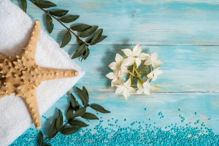 Spa and wellness setting with flowers, and white towel on old wooden background. Blue dayspa nature set. copyspace. Vacation concept. flat lay. top view