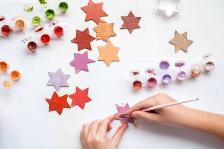 A child carves a star from cardboard. Christmas decoration, Christmas garland, hand made and Zero waste. Hands of a child on a white background. Div.