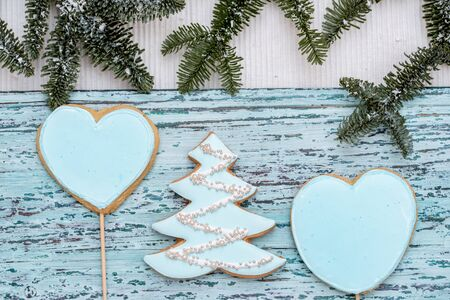 Christmas gingerbread on a white mitten. on a blue wooden background. New Year card. Christmas tree on a stick. sweet candy.