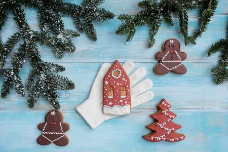 Christmas gingerbread on a white mitten. on a blue wooden background. New Year card. Christmas tree with balls and a house.