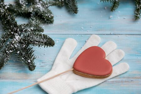 Christmas gingerbread on a white mitten. on a blue wooden background. Red heart on a stick. sweet candy.New Year card. 写真素材