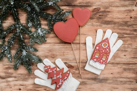 Whites mittens on wooden background. Red Christmas gingerbread cookies. New Year card