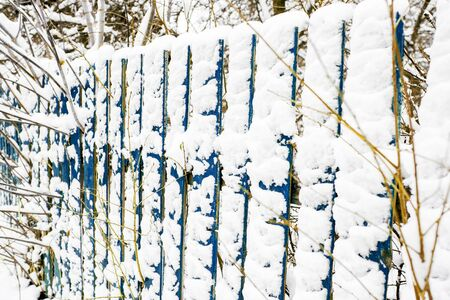 Snow-covered old rural wooden fence. Winter in the village. Snow and icicles are everywhere. New Year and Christmas mood. Severe frost. Ice in the puddles. Slippery roads.Copy space