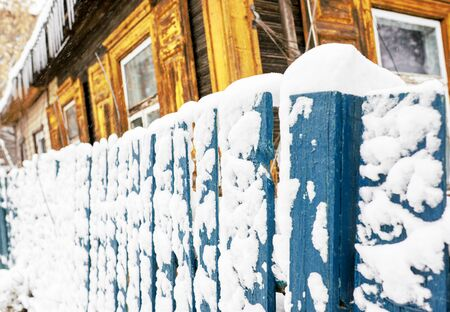 Snow-covered blue old rural wooden fence.