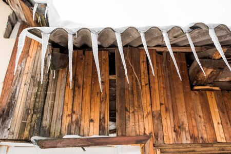 Snow-covered old rural wooden fence.Icicles hang from the roof of a wooden house in the countryside, on a frosty cloudy day.