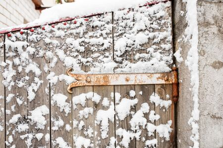 Winter in the village. Wooden frozen fence. Snow and icicles are everywhere. New Year and Christmas mood. Severe frost. Ice in the puddles. Slippery roads. Copy space 写真素材