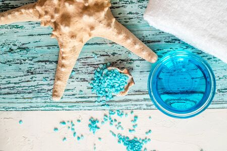 Beautiful blue spa composition. blue sea salt, liquid soap, starfish, shells and a white bath towel.babys hand takes soap