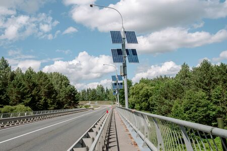 Solar energy panel. Blue sky with clouds, wide highway autobahn and forest.Renewable solar energy concept