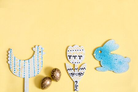 Candy color easter Blue and Gold Quail Eggs. Wooden painted chicken, hare and flower on a yellow background. gray napkin